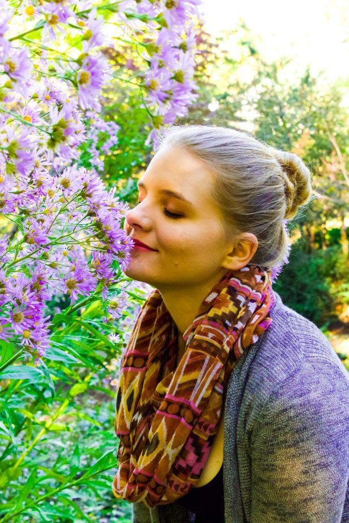 Blond woman smelling flowers in a field